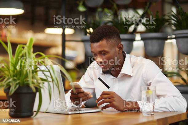 African Businessman Working With Laptop And Paying With Credit Card Stock Photo - Download Image Now
