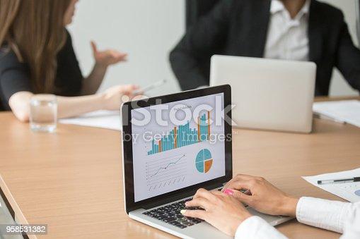 istock African businesswoman analyzing statistics on laptop at group meeting, closeup 958531382