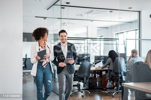 African businesswoman and her Caucasian coworkers using digital tablet and walking in the office