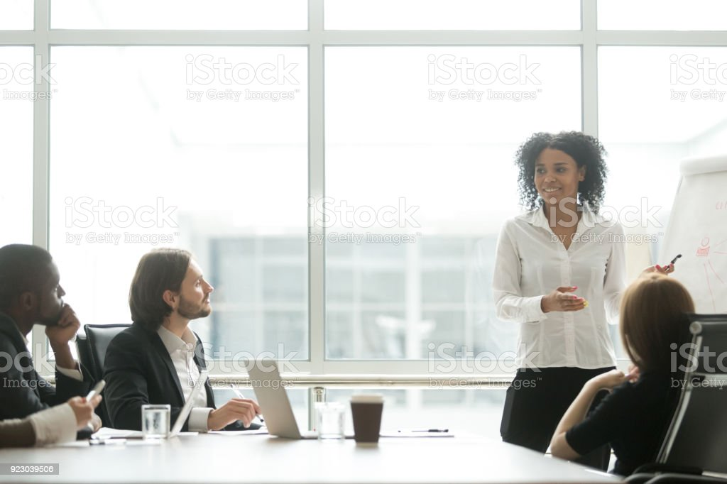 African businesswoman giving presentation working with flipchart in meeting room stock photo