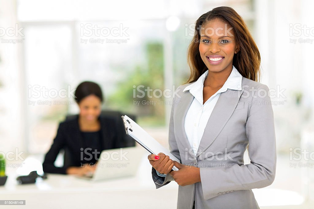 african businesswoman holding clipboard stock photo