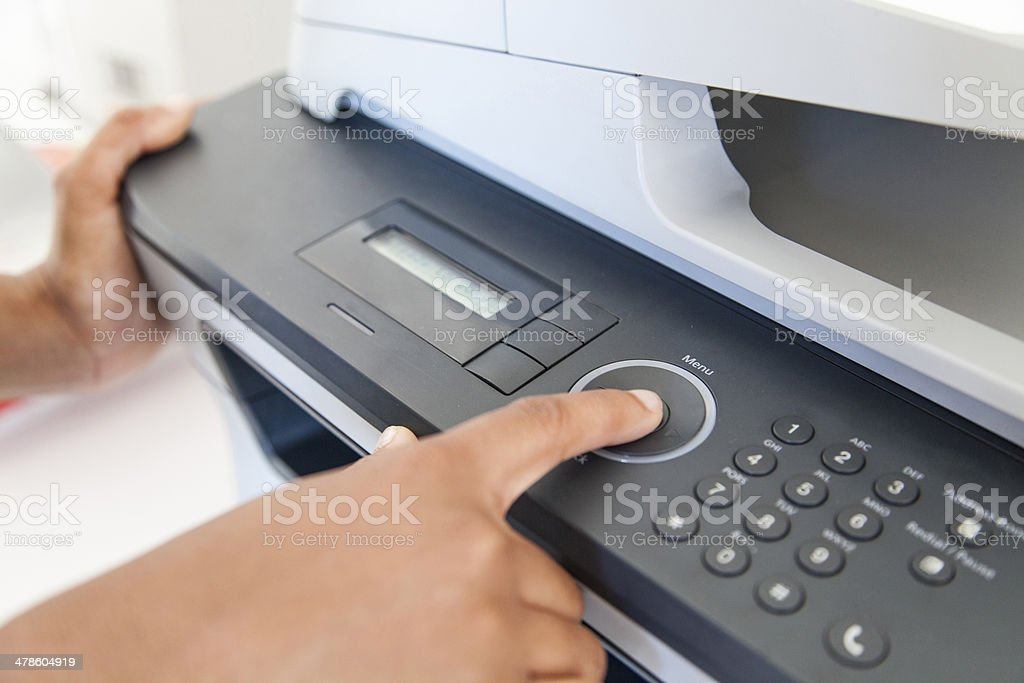 African businesswoman pressing the start button to print stock photo