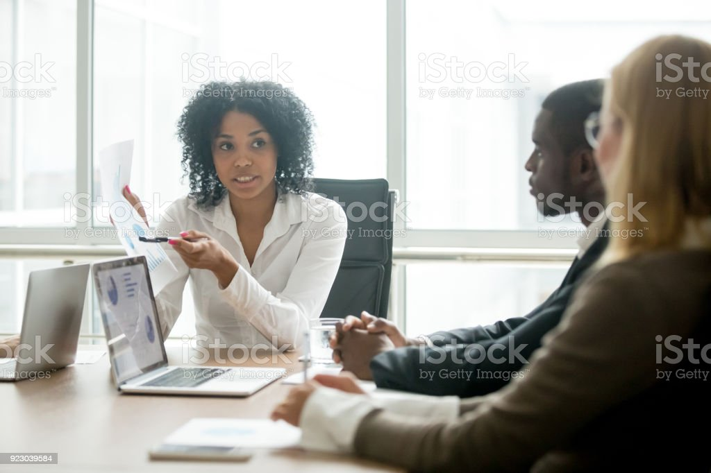 African businesswoman showing good statistics convincing multiracial partners at negotiations stock photo