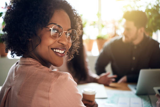 African businesswoman smiling during a boardoom meeting in an office stock photo