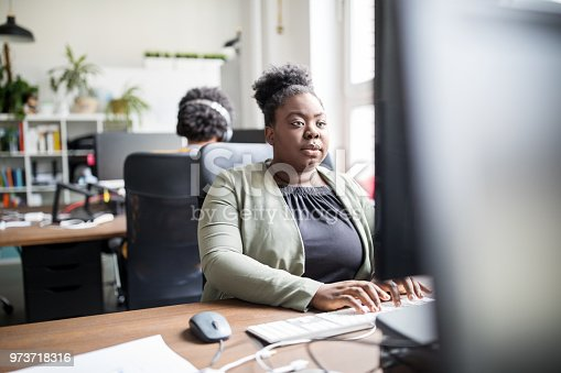 Young african woman sitting at her office desk and working on computer. Female professional working in office.