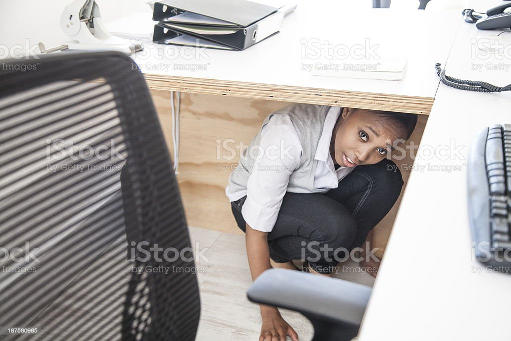 African Businesswomen hiding away from her boss stock photo