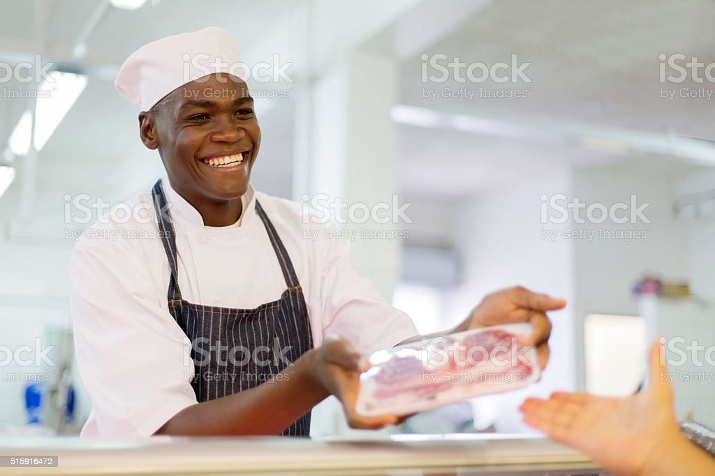 african butcher selling beef to customer stock photo