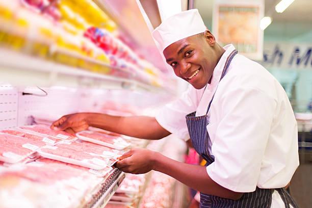 african butcher working in butchery stock photo