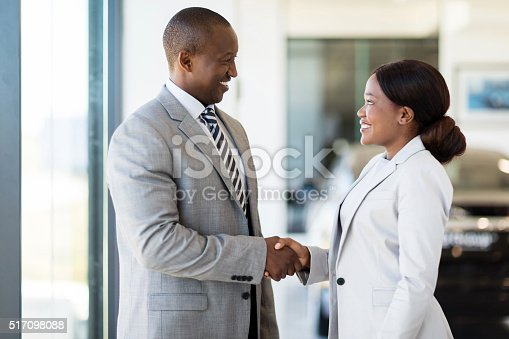 istock african car dealer handshake with customer 517098088