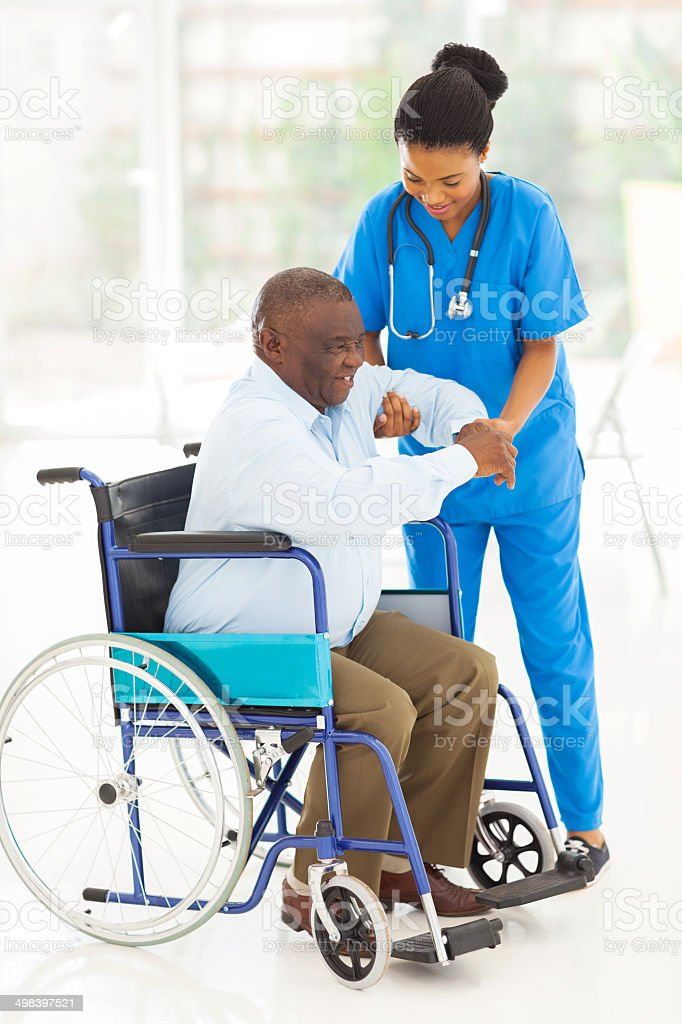african caregiver helping senior man getting up stock photo