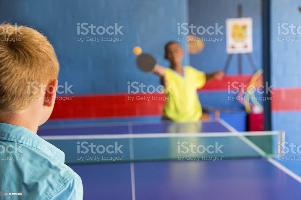 African & caucasian children playing table tennis stock photo