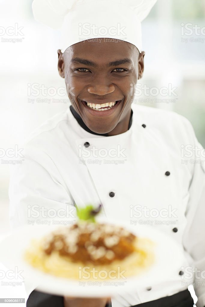 African chef in hotel kitchen presenting pasta stock photo