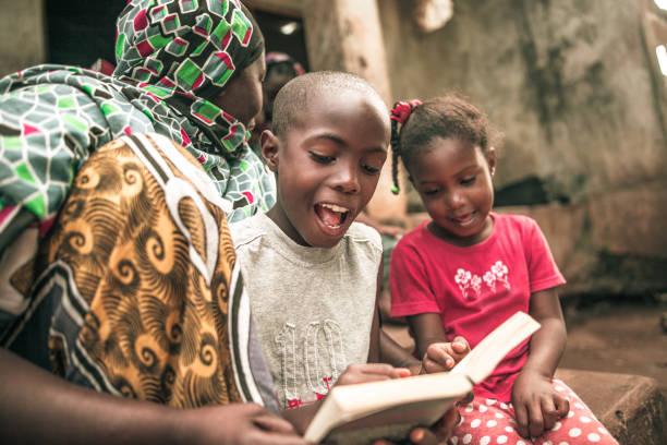 afrikanische kinder ihre hausaufgaben bei der mutter - haushaltsbuch führen stock-fotos und bilder