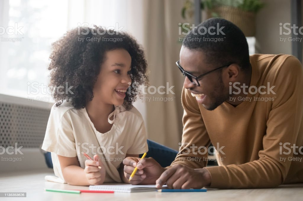 African child girl drawing with pencils having fun with dad royalty-free stock photo