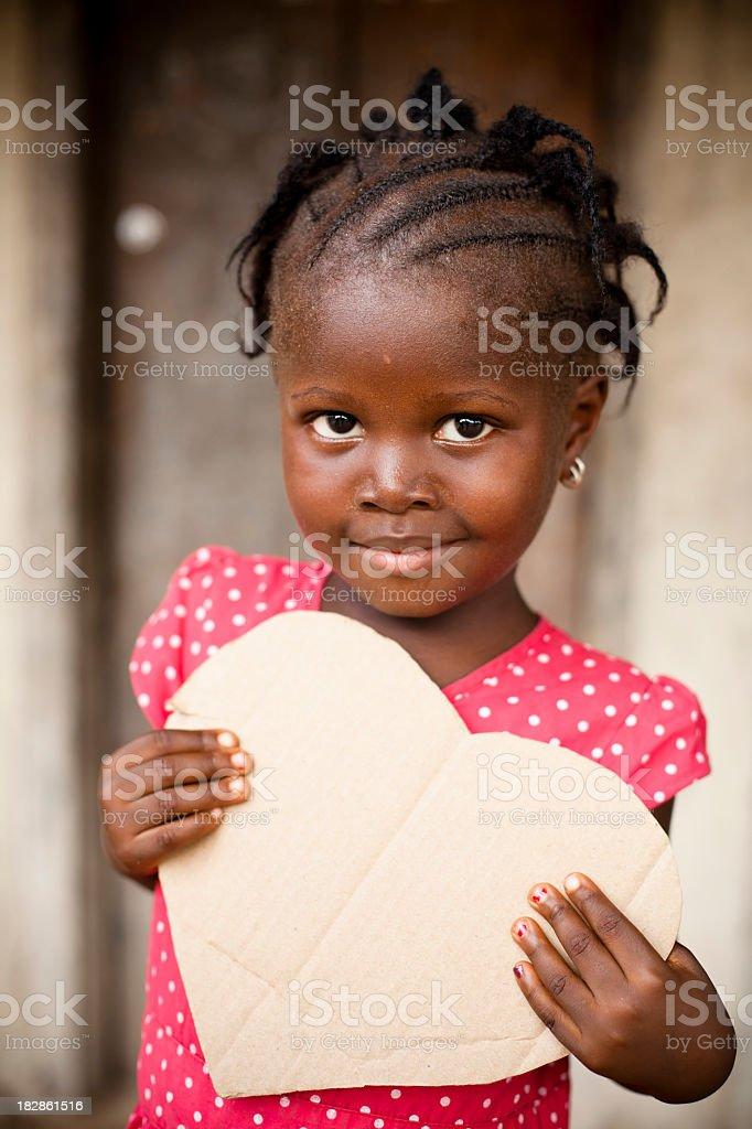 African child holding heart shaped cardboard sign stock photo
