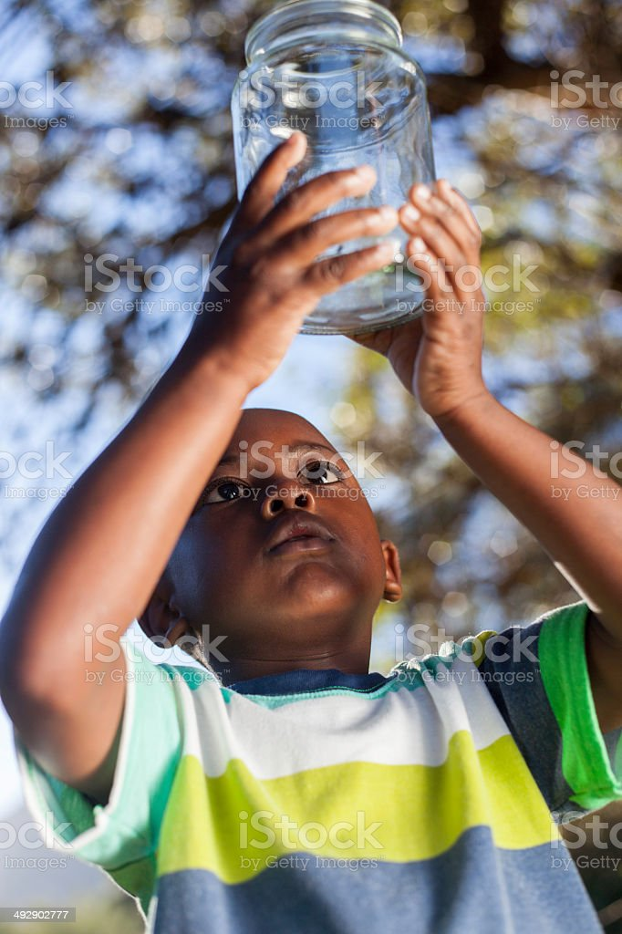 African child inspects bug in glass jar in his garden stock photo