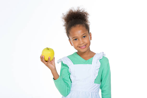 african child with yellow fruit smiling at the camera stock photo