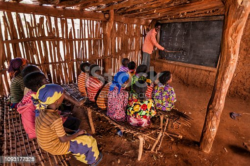 African children during english class in very remote school. The bricks that make up the walls of the school are made of clay and straw. There is no light and electricity inside the classroom