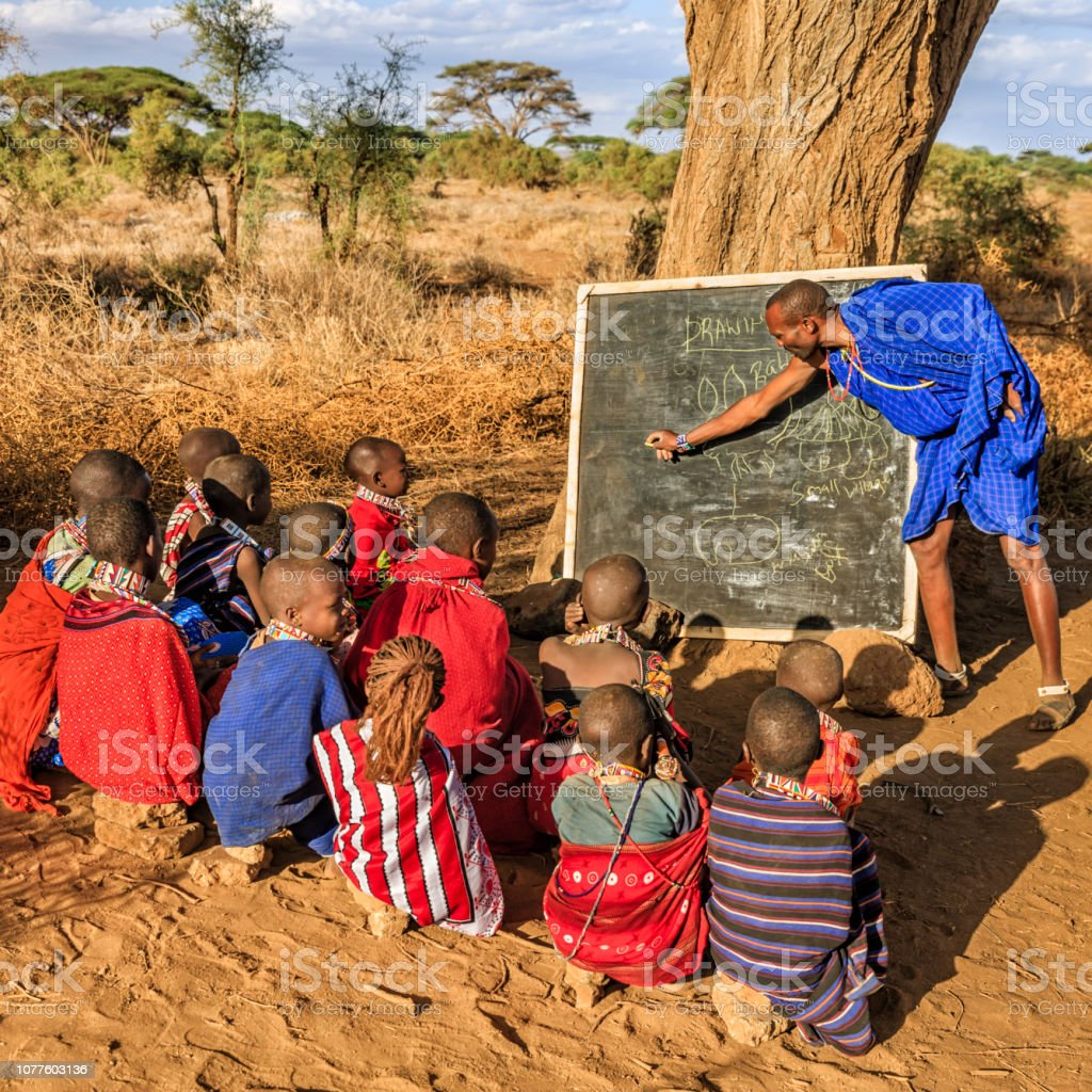 African children from Maasai tribe during classes under the acacia...