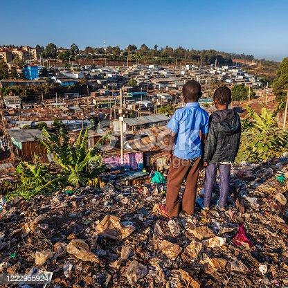 African children standing in trash and looking at houses in Kibera slum, Kenya, East Africa. Kibera is the largest slum in Nairobi, the largest urban slum in Africa, and the third largest in the world