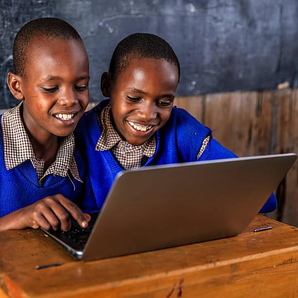 African children using a laptop inside classroom, Kenya stock photo