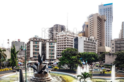 Lagos, Nigeria - February 15, 2016: Tinubu Square on Lagos Island - surrounded by high-rise buildings, park and fountain in the middle.