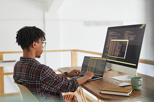 African-American IT developer typing on keyboard with black and orange programming code on computer screen and laptop in contemporary office interior, copy space