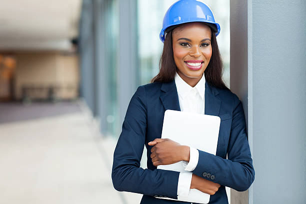 african construction engineer holding laptop computer stock photo
