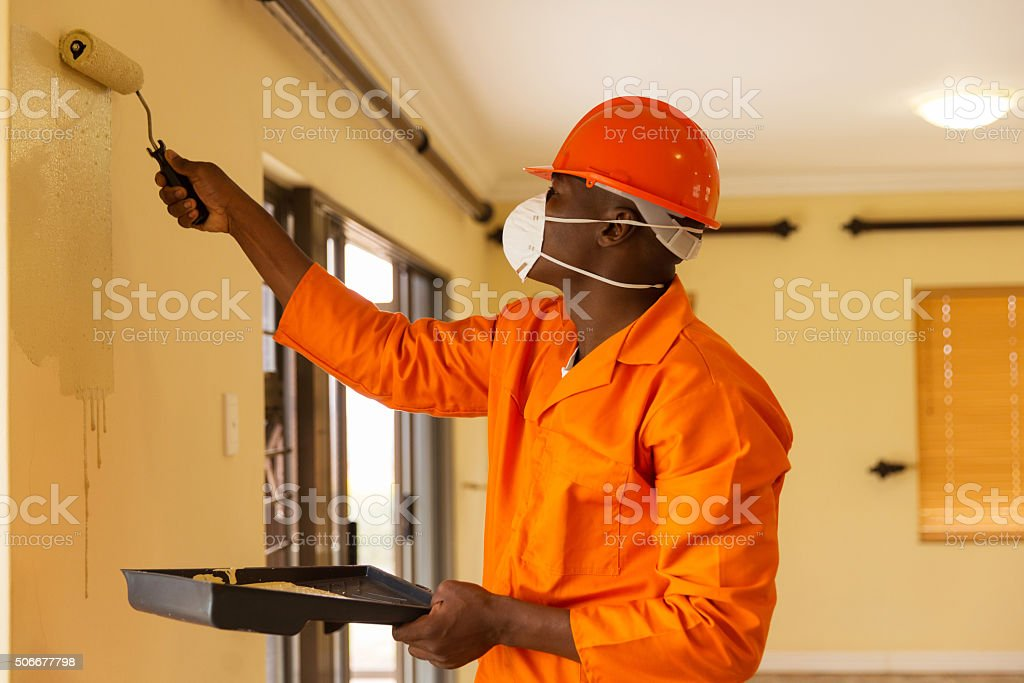 african construction worker painting the wall stock photo