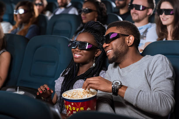 African couple at the cinema Spectacular film. Closeup portrait of an attractive young African couple smiling happily while watching a movie at the cinema 3 d glasses stock pictures, royalty-free photos & images