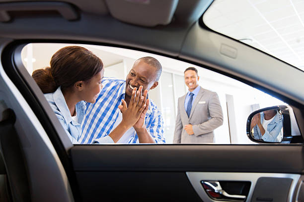 african couple at the dealership buying new car stock photo