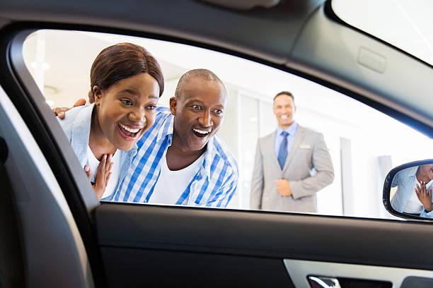 african couple choosing luxury car stock photo