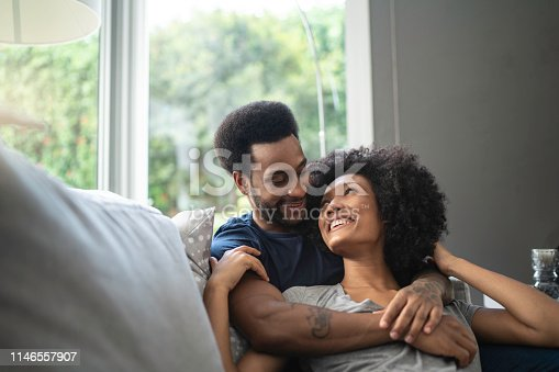 istock African couple lying down and having romantic moment on couch 1146557907