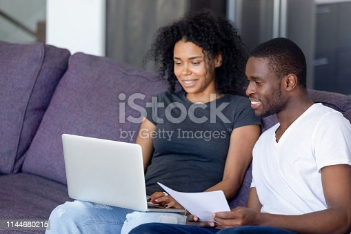 istock African couple sitting on couch checking bills using computer 1144680215