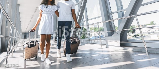 istock African couple walking with luggage in airport 1165466429