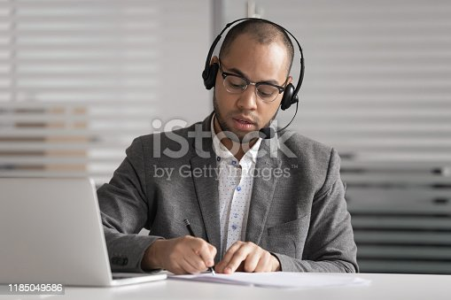 istock African customer support agent wear headset write notes make videocall 1185049586