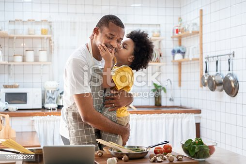 istock African Cute little boy in yellow casual kissing Dad while cooking at home together. Happy smiling African-American Father while hug and carry his son in kitchen. Joyful Black family, Love emotion. 1227393227