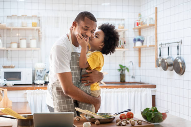 African Cute little boy in yellow casual kissing Dad while cooking at home together. Happy smiling African-American Father while hug and carry his son in kitchen. Joyful Black family, Love emotion. stock photo