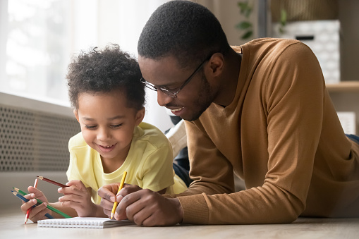 istock African dad and little toddler son draw with colored pencils 1135353588
