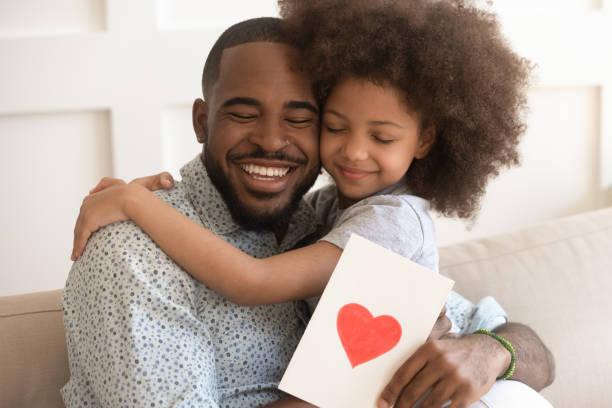 pai africano que abraça a filha que prende o cartão no dia de pais - feliz dia dos pais - fotografias e filmes do acervo