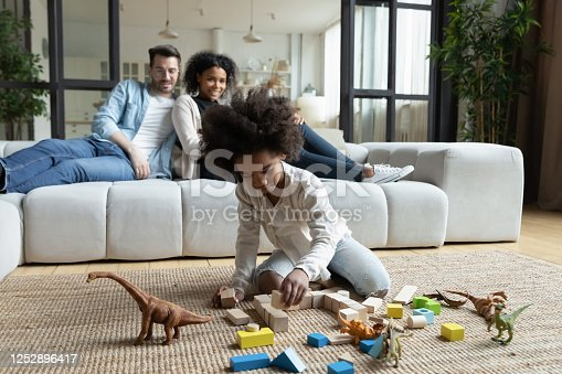 African daughter play on floor with wooden blocks set and dinosaur toys while multi ethnic parents sitting on sofa in living room, homeowners spend time at new home. First house family weekend concept