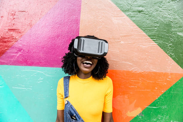 African decent woman wearing virtual reality goggles stock photo