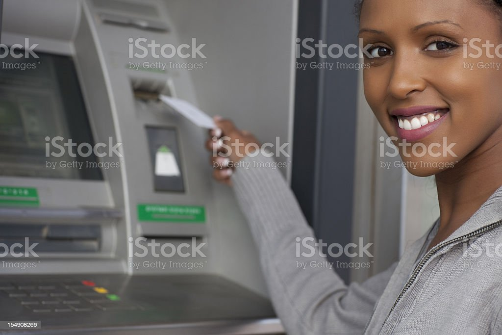 African decent woman withdrawing money from credit card at ATM. stock photo