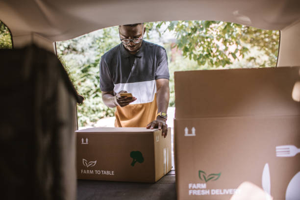african delivery man checking delivery address in the car trunk - side hustle stock pictures, royalty-free photos & images