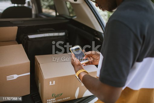 istock African Delivery Man Checking Delivery Address In The Car Trunk 1170736816