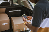 Young African delivery man using mobile app to check delivery address before delivery. Delivering meal kit.