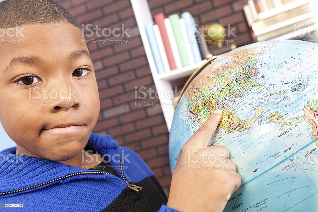 Back to school time! African descent, elementary boy enjoys learning...