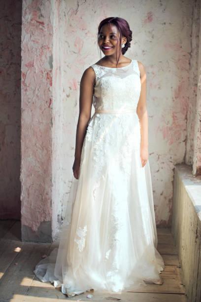 afrikanischer herkunft braut im weißen hochzeitskleid fröhlich - verlobungskleider stock-fotos und bilder
