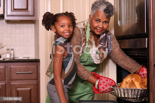 Family members work together in grandmother's home kitchen to prepare Thanksgiving dinner.  Grandmother takes roasted turkey out of oven with help from granddaughter.