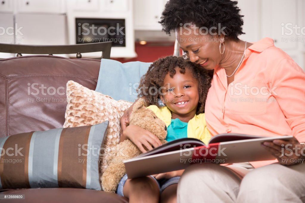 African descent family reading books together at home. stock photo